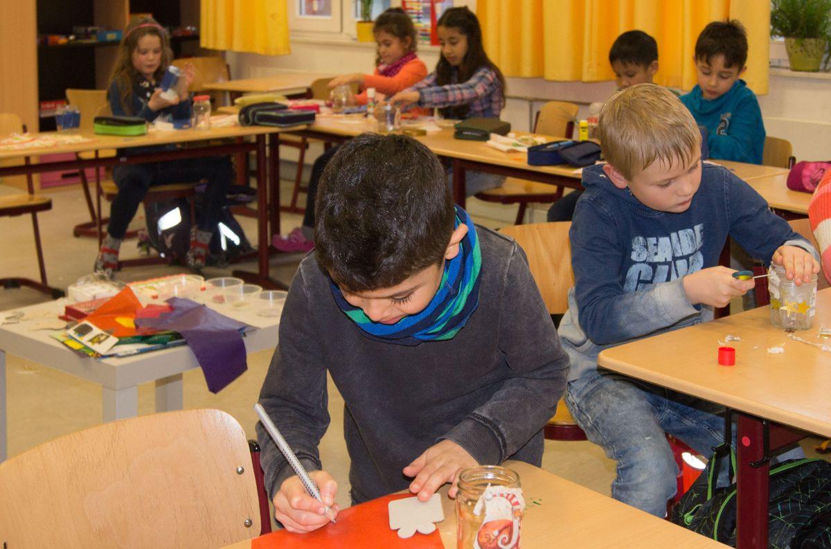 Die Kinder der 2a basteln weihnachtliche Windlichter.